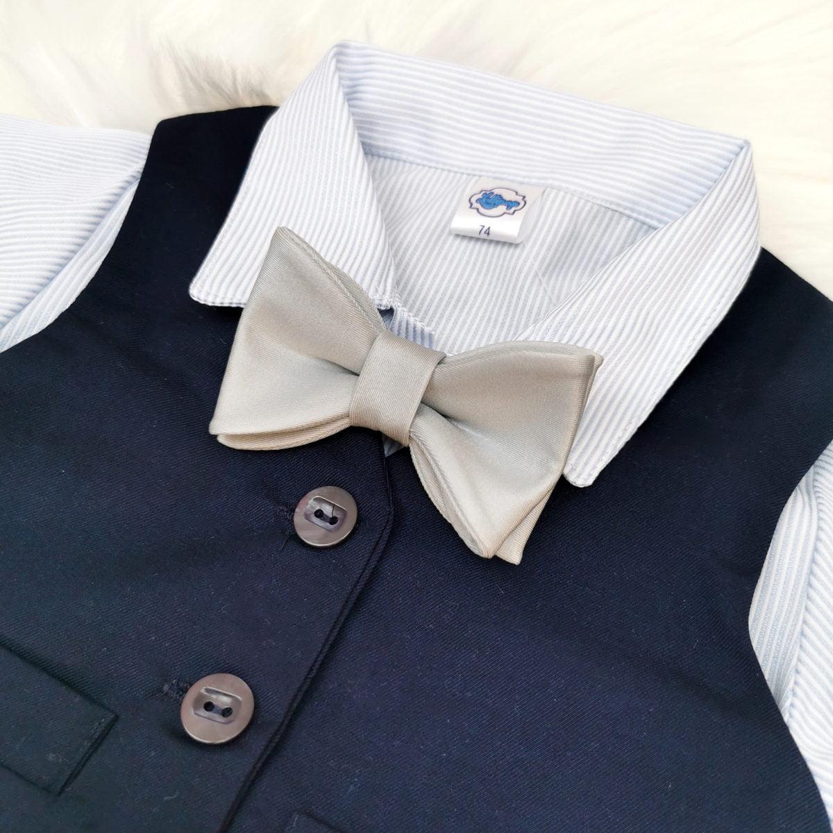 srebrna leptir mašna na tamno plavo odijelo